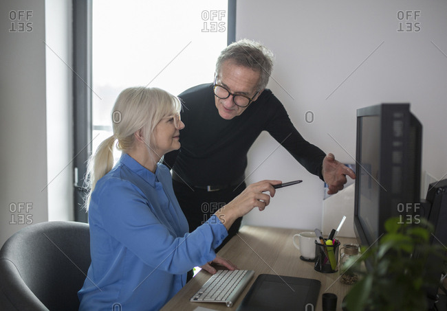 Two senior colleagues working together at desk in office