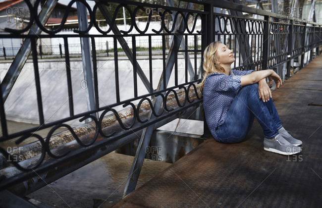 Blond woman sitting on bridge, taking a break