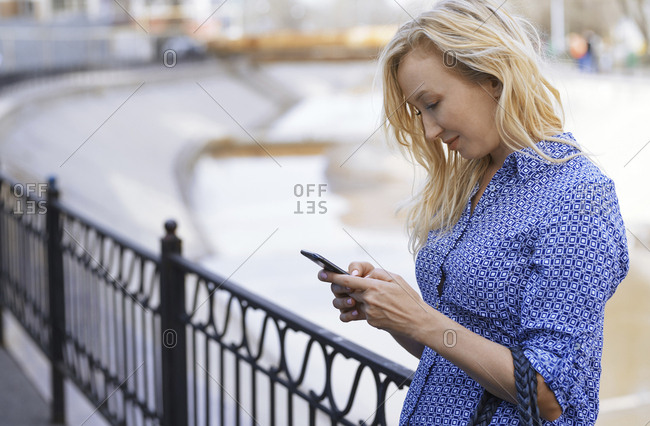 Blond woman using smartphone on a street