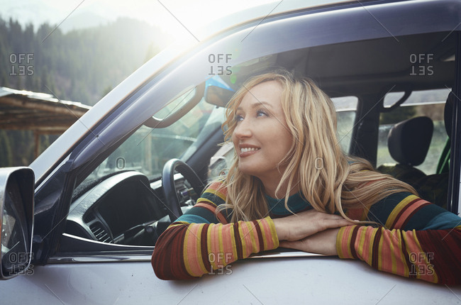 Woman sitting in car, looking at view on a road trip