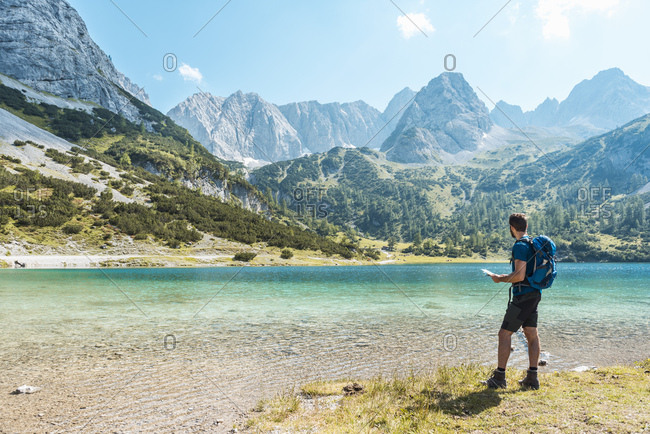 Austria, Tyrol, Man hiking at Seebensee Lake, looking at map