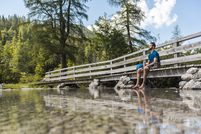 Austria, Tyrol, Hiker at Lake Seebensee sitting on boardwalk, taking a break