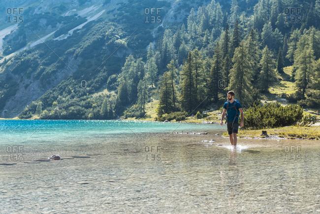 Austria, Tyrol, Hiker at Lake Seebensee walking ankle deep in water