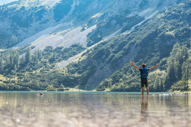 Austria, Tyrol, Hiker at Lake Seebensee standing ankle deep in water, with raised arms