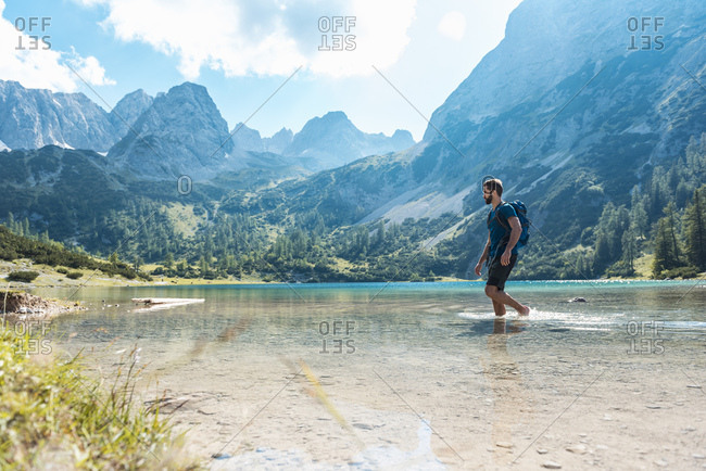 Austria, Tyrol, Hiker at Lake Seebensee walking ankle deep in water
