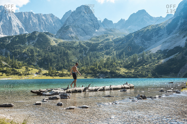 Austria, Tyrol, Young man at Lake Seebensee balancing on tree trunk