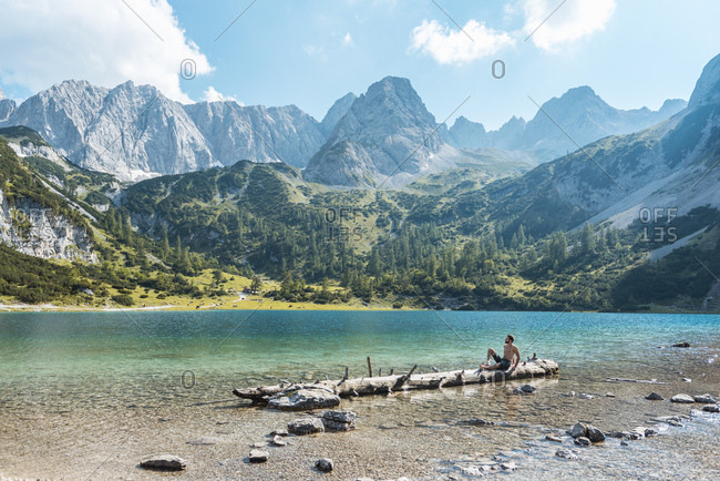 Austria, Tyrol, Young man at Lake Seebensee sitting on tree trunk
