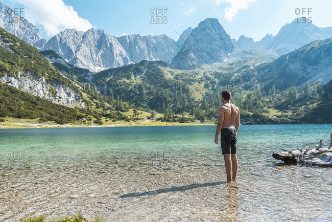 Austria, Tyrol, Young man at Lake Seebensee standing ankle deep in water