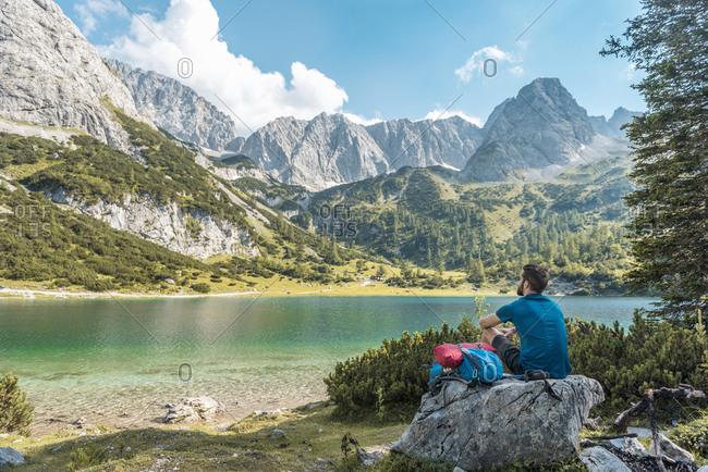 Austria, Tyrol, Hiker taking a break, sitting on a rock, looking at lake