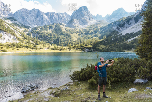 Austria, Tyrol, Hiker taking selfie with his smartphone at Lake Seebensee