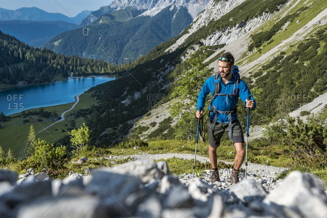 Austria, Tyrol, Young man hiking in the mountains at Lake Seebensee