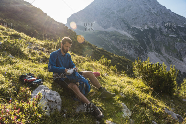Austria, Tyrol, Hiker taking a break, sitting on a rock, searching his rucksack