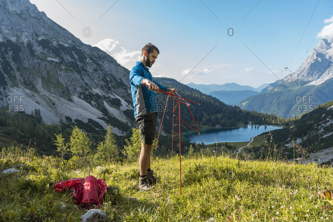 Austria, Tyrol, Hiker setting up his tent in the mountains at Lake Seebensee