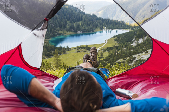 Austria, Tyrol, Hiker relaxing in his tent in the mountains at Lake Seebensee