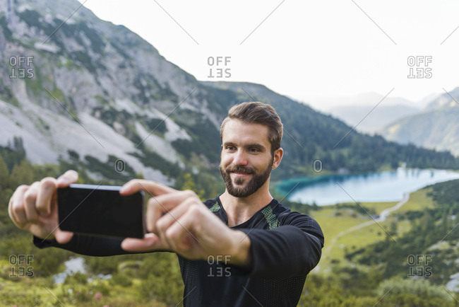 Austria, Tyrol, Hiker taking selfie with his smartphone at Lake Seebensee