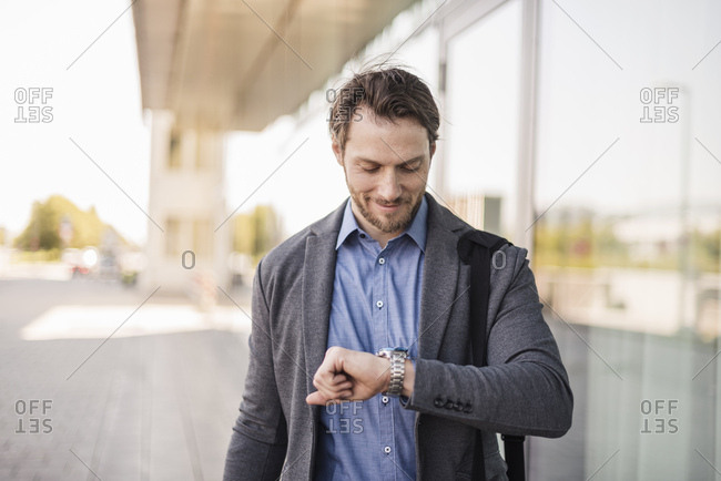 Smiling businessman with laptop bag checking the time