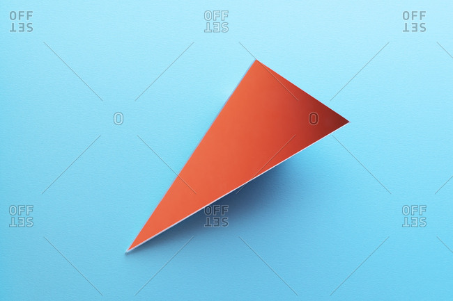 Triangle shaped mirror on light blue ground, 3D Rendering