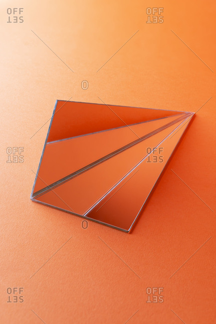 Triangle shaped mirrors on orange background
