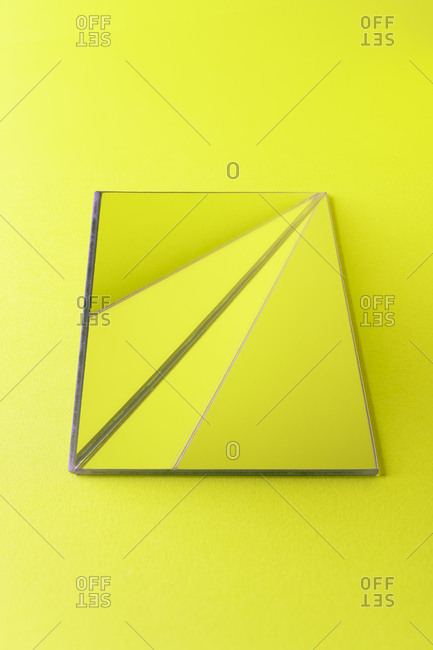 Triangle shaped mirrors over lime green background