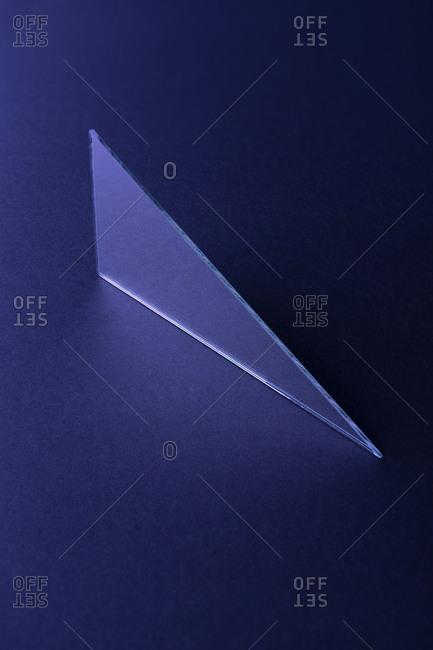 Triangle shaped mirror on dark blue ground, 3D Rendering