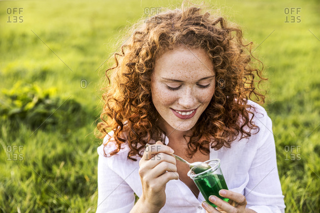 Portrait of smiling young woman eating jelly on meadow