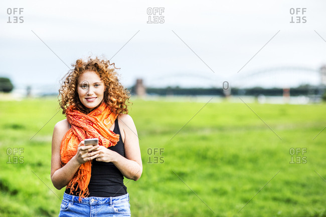 Portrait of smiling young woman with curly red hair on a meadow