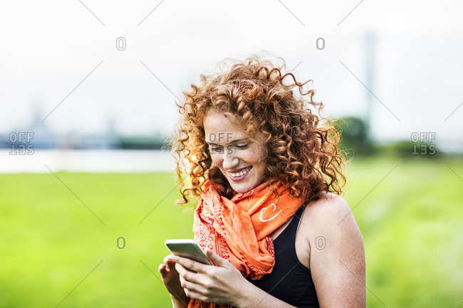 Portrait of happy young woman with curly red hair looking at cell phone