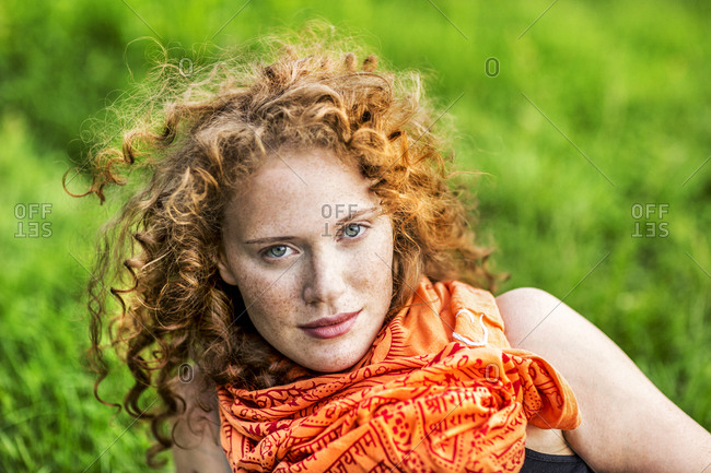 Portrait of freckled young woman with curly red hair wearing orange scarf