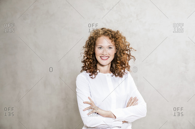 Portrait of laughing redheaded young woman with arms crossed