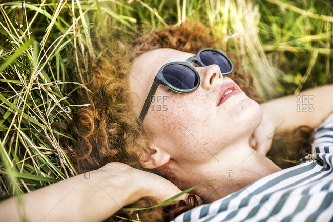 Young woman wearing sunglasses relaxing on a meadow