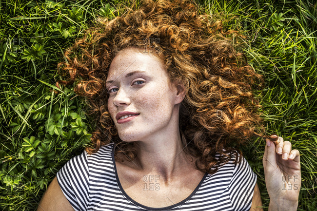Portrait of smiling young woman lying on a meadow