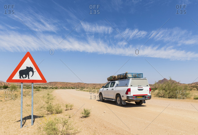 Namibia, Erongo Region, off, road vehicle on sand track, deer crossing sign with elephant