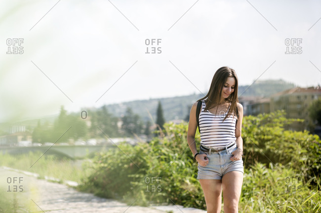 Smiling young woman walking on a rural path in summer