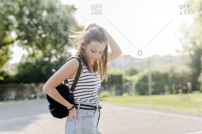 Portrait of smiling young woman with backpack outdoors in summer