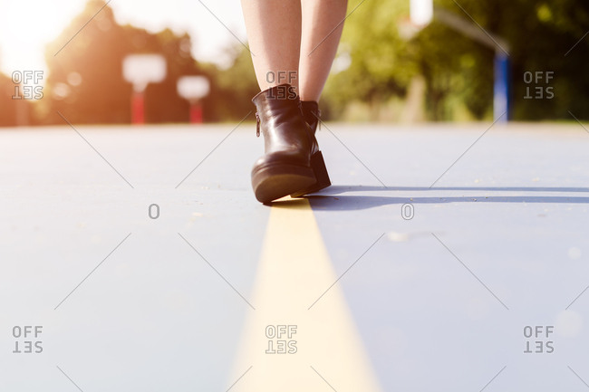 Legs of a woman wearing ankle boots walking on a line on sports ground
