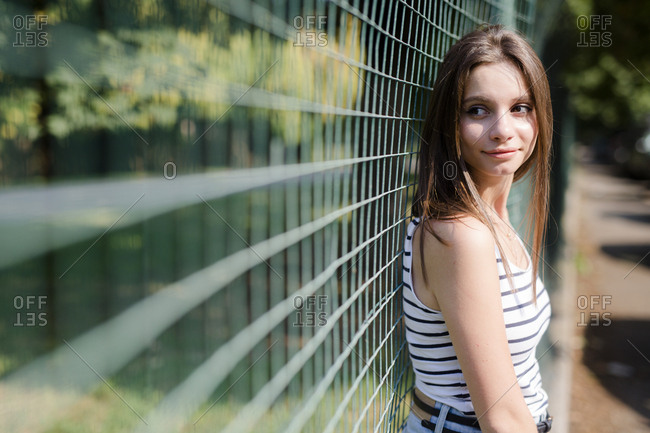 Portrait of smiling young woman standing at a fence