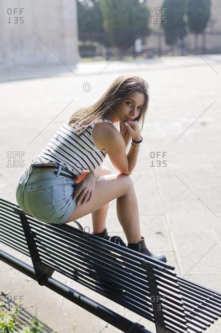 Portrait of smiling young woman sitting on a bench