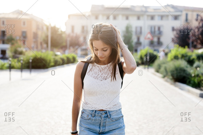 Young woman in the city looking down