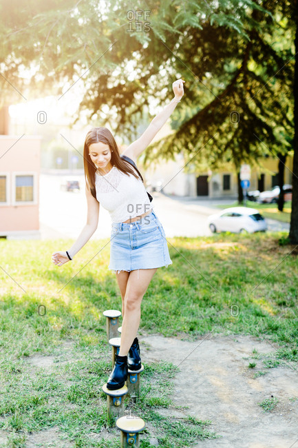 Young woman balancing on posts
