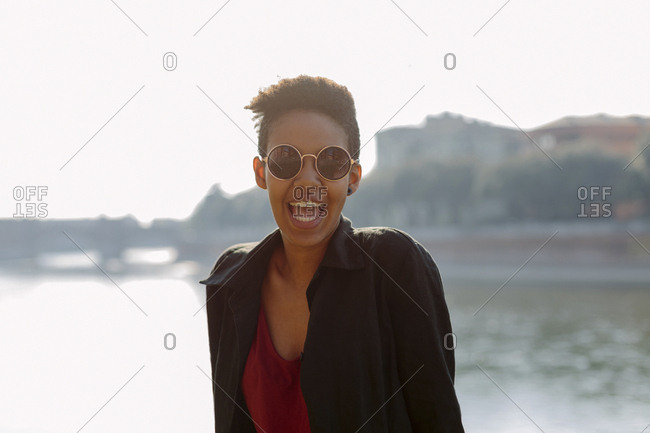 Italy, Verona, portrait of laughing young woman wearing sunglasses