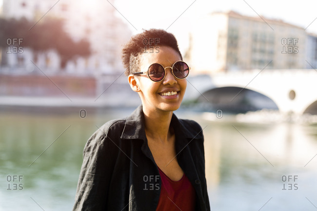 Italy, Verona, portrait of smiling young woman in front of Adige River