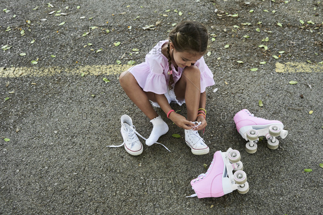 Little girl wearing pink blouse and braids tying shoes after roller skating