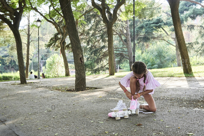 Little girl tying pink roller skates in a park