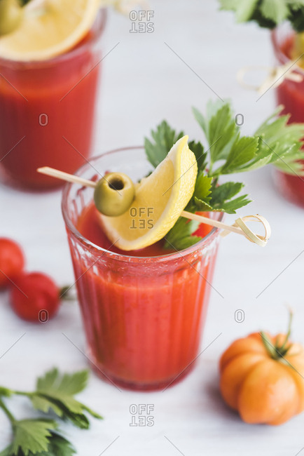 Glasses of fresh spicy tomato juice with cellery garnished with lemon slice, green olive and parsley