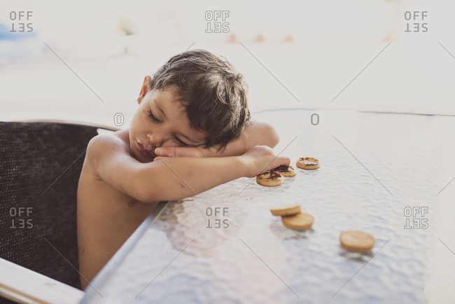 Portrait of little boy falling asleep while eating chocolate cookies