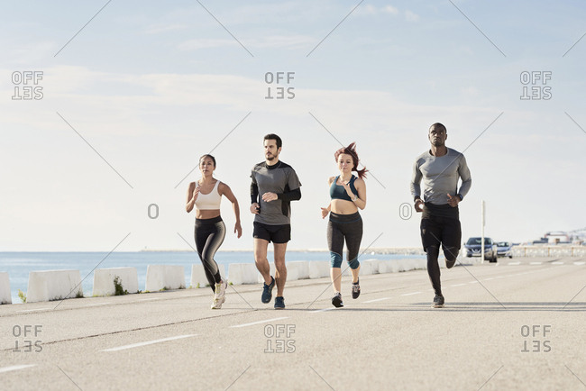 Group of sportspeople jogging at harbor
