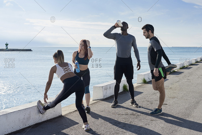 Group of sportspeople during break, stretching and training