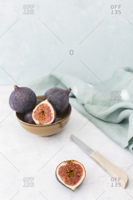Sliced and whole fresh figs, kitchen knife and cloth