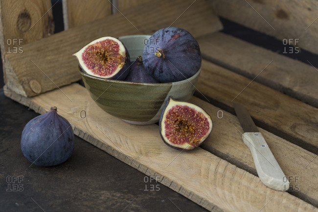 Sliced and whole fresh figs, kitchen knife and wooden box