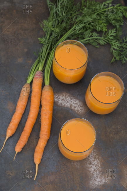 Three glasses of fresh carrot juice and three carrots